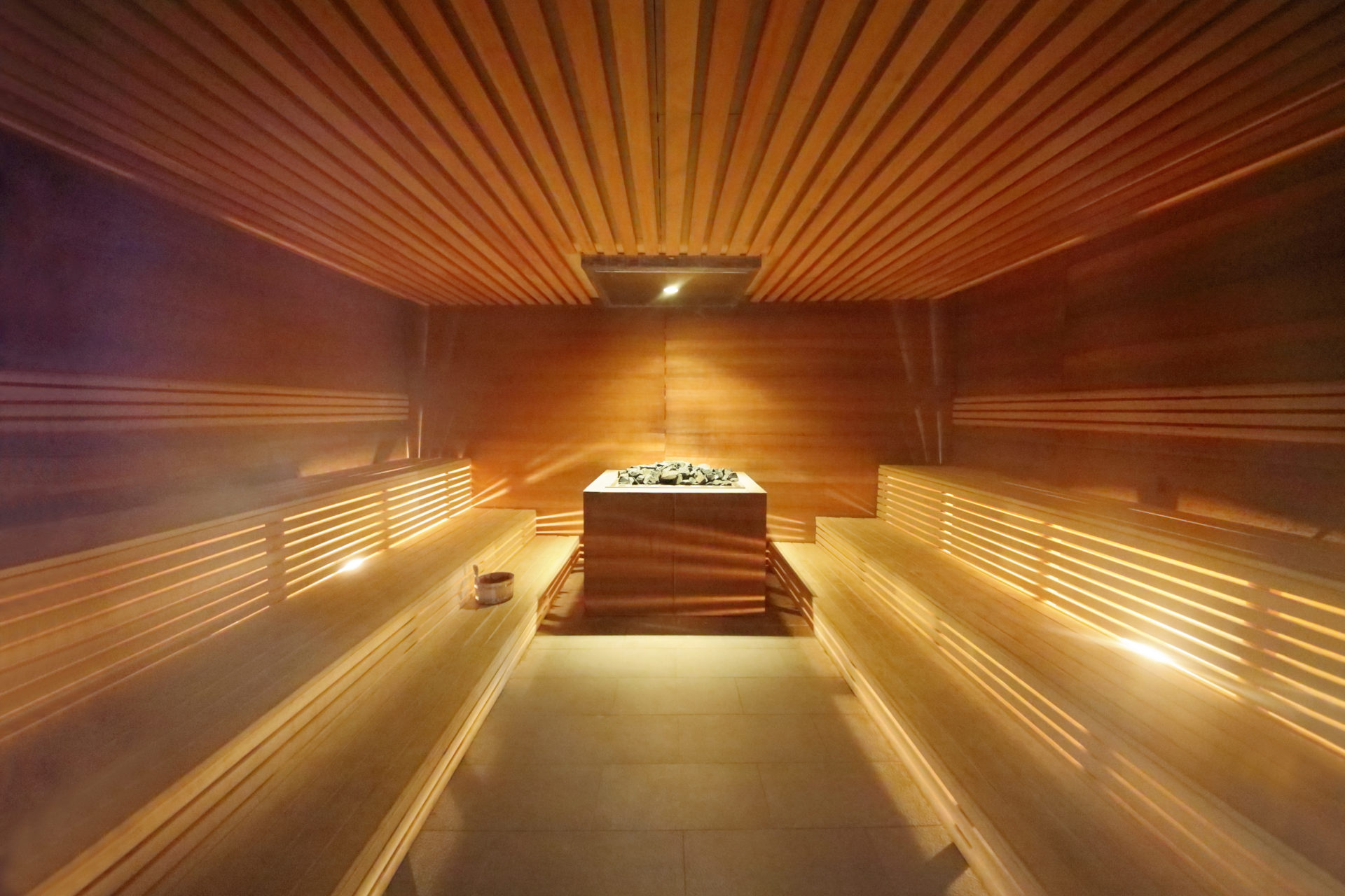 Interior Inside The Sauna Room With Wooden Benches And Hot Stones